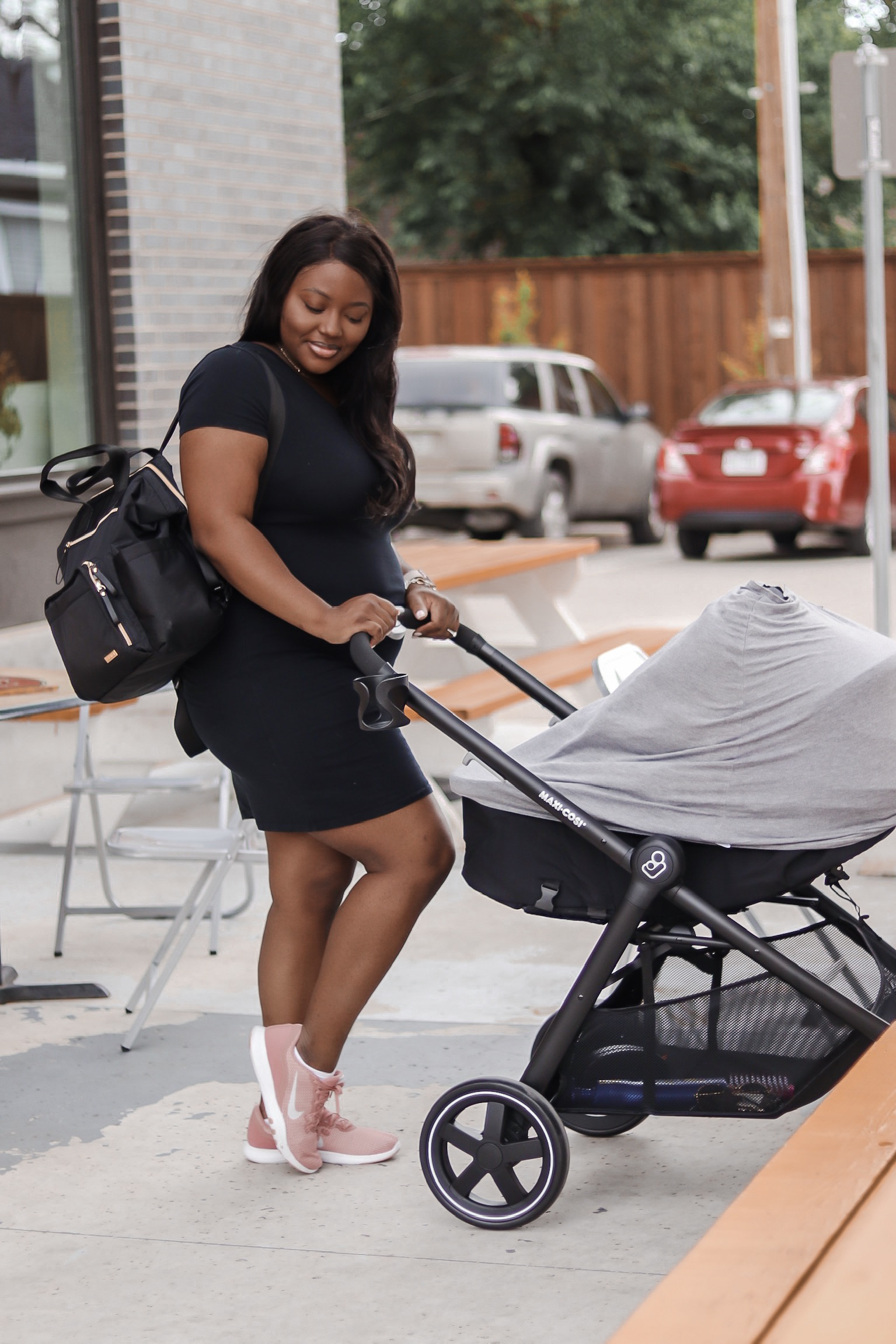 mom life, wearing black dress, rose gold nike shoes, skip hop baby bag and maxi cosi stroller