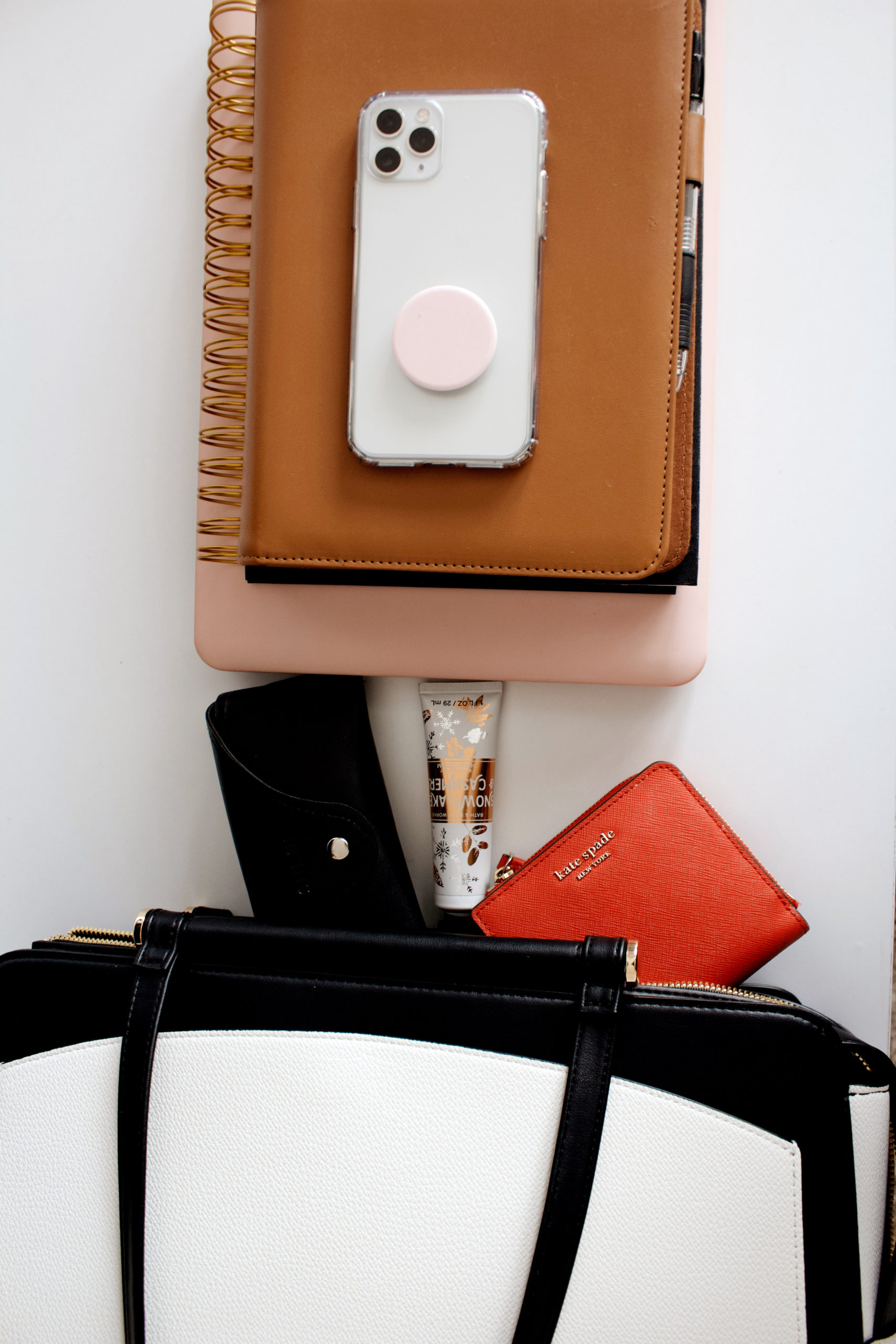 items spilling out of work bag including iPhone 11 Pro with pink pop socket.