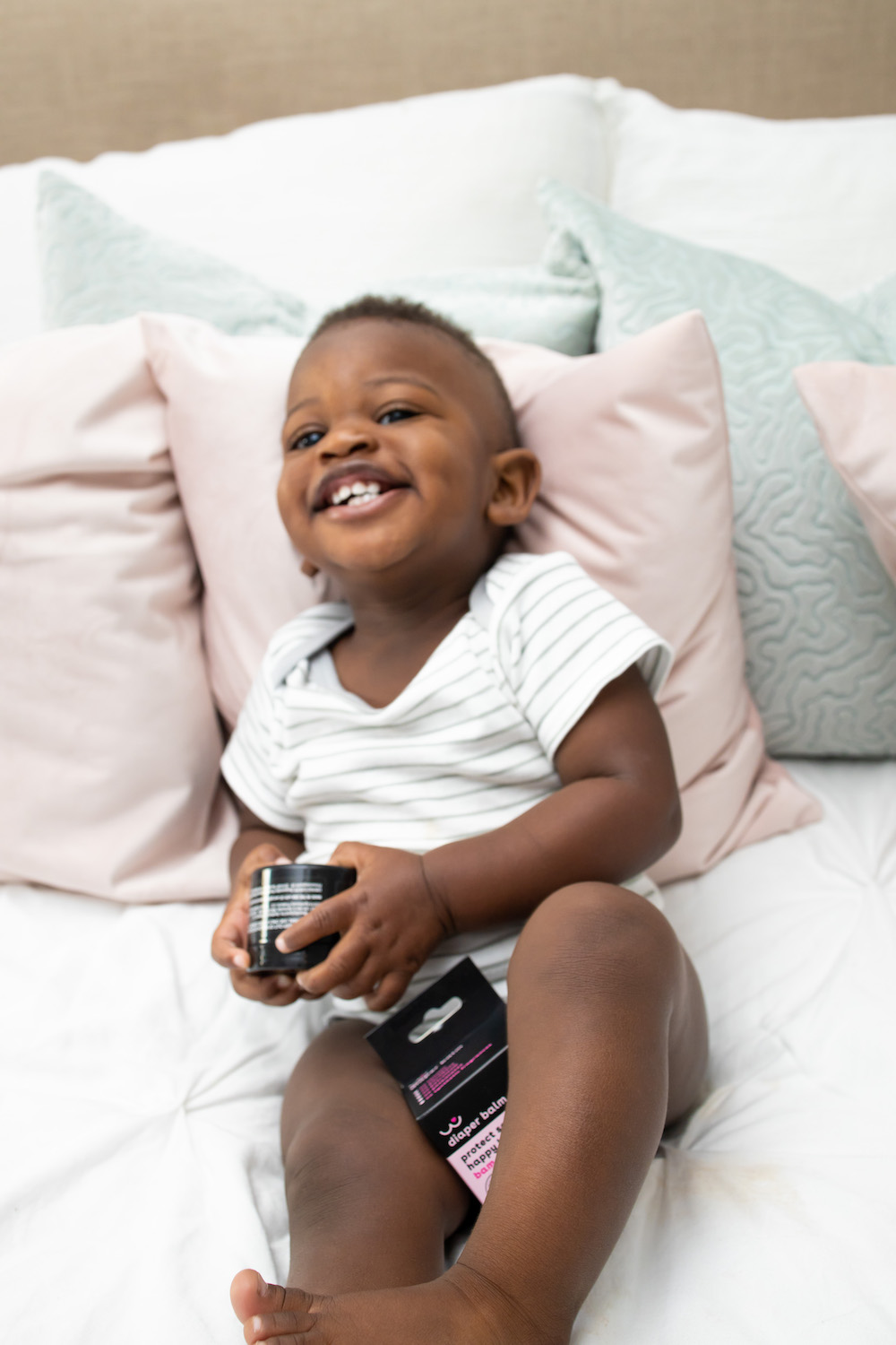 Baby boy laughing in bed with soothing products